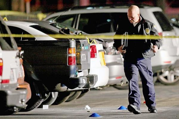 A member of the Newport Beach police department surveys the scene where shots were fired in the parking lot facing Macy's at Fashion Island on Saturday.