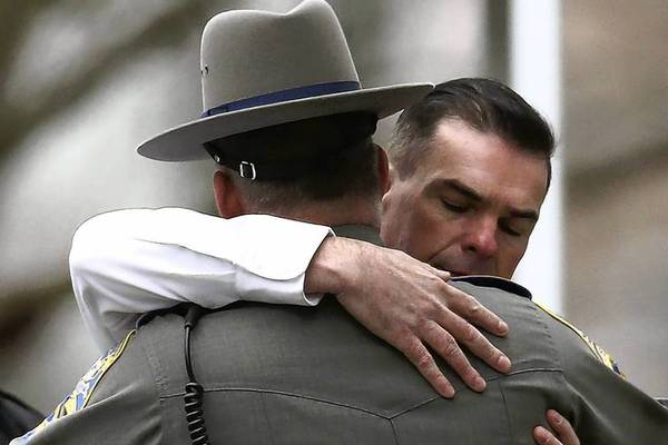 Two law enforcement officers embrace as they arrive for the funeral services of six year-old Noah Pozner, who was killed in the shooting massacre in Newtown, Conn., at Abraham L. Green and Son Funeral Home in Fairfield, Connecticut. Today is the first day of funerals for some of the twenty children and seven adults who were killed by 20-year-old Adam Lanza on December 14, 2012.