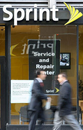 New York residents walk past a shop offering Sprint Nextel mobile phone service in New York in 2008.
