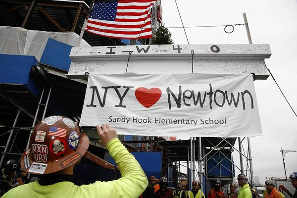 "Union workers from Iron Workers Local 40 raise a beam with a banner attached supporting victims of the Newtown, Connecticut school shooting during the Whitney Museum ""Topping Out"" Beam-Signing Ceremony in New York."