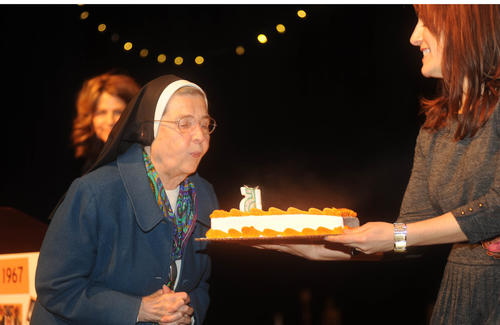 Sister Kathleen Marie Engers blows out the candles on the birthday cake during the 45th birthday celebration for Pumpkin Theatre at St. Timothy's School Sunday afternoon.
