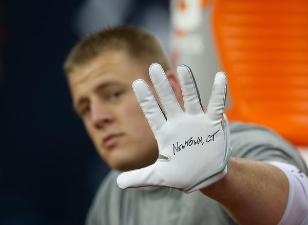 J.J. Watt #99 of the Houston Texans displays a glove to remember the victims of the massacre at Sandy Hook Elementary School in Newtown, Connecticut prior to the start of the game against the Indianapolis Colts at at Reliant Stadium on December 16, 2012 in Houston, Texas.