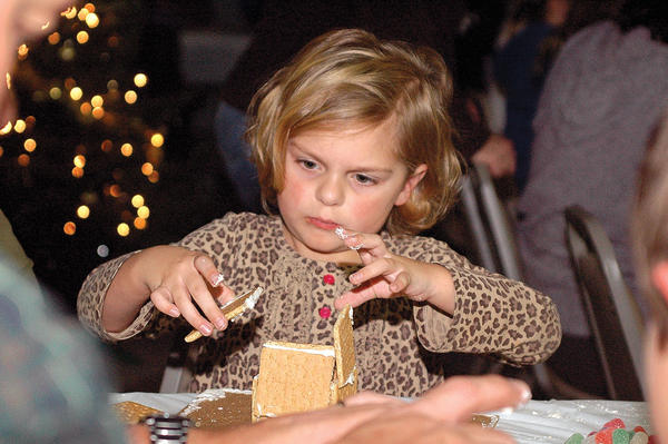 Lily Roberts prepares to attach a wall to the side of her gingerbread house Friday at the Winchester-Clark County Parks and Recreation Department¿s Gingerbread House Party at College Park Gym, top photo. Karma Combs, at right, sneaks a bite while decorating her gingerbread house. Below, Judy Lewis helps Alexis Littrell decide what to do next with her house.