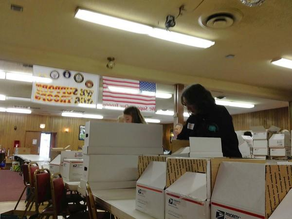 Bonnie Hale prepares boxes to be sent to American troops at the Batavia VFW .