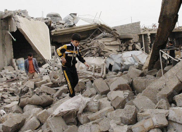 A boy walks in rubble at the scene of a car bomb attack in Mouafaqiyah, an Iraqi village inhabited by families from the Shabak ethnic group, near the city of Mosul.