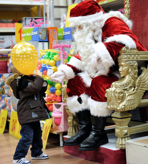 A Santa Claus gives a balloon to a boy, on December 15, 2012 in a toy store in Lille, northern France.