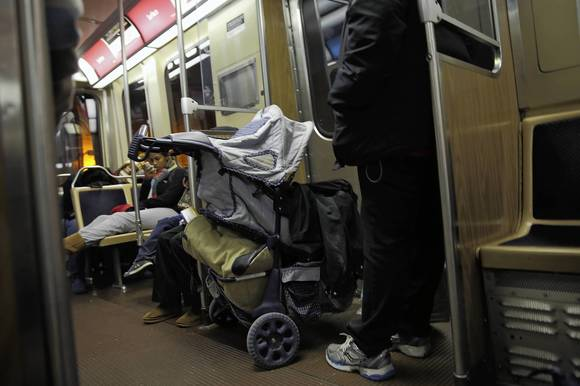 A woman rides with a stroller on a Red Line train south of the Roosevelt Road station last week.