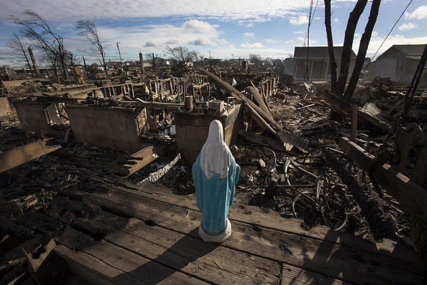 A statue of the Virgin Mary stands over houses destroyed by fire in New York City during Superstorm Sandy.