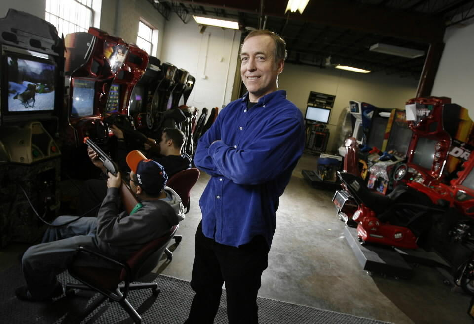 Eugene Jarvis, video-game pioneer, at a testing area filled with video games, including the Big Buck safari game, being tested by Roberto Bontemps, left, and Justin Cappozzo at Raw Thrills, Jarvis' Skokie-based gaming company.