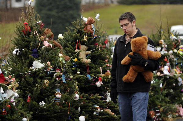 "Stephen Post, of Cromwell, tries to decide which Christmas tree to leave a teddy bear for the victims of the Sandy Hook School massacre. Post has had the bear since he was nine-years-old and wanted to leave it with one of the twenty six trees lining the road near the school. He had left the bear with his grandfather when he was in intensive care years dying from a heart attack. The bear watched over his grandfather, he said. ""Now they need some watching over,"" he said, of the children."