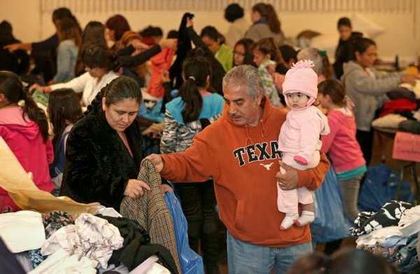 Antonio Vilchis, right, of Lake Forest, carries his granddaughter Cassidy Muniz, 1, as he hands a free item of clothing off to his wife Maria during a Laguna Beach Woman's Club charity event on Friday.