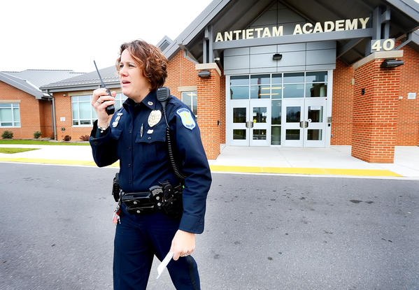 Hagerstown Police Department School Resource Officer Heather Aleshire speaks with school administration via walky-talky Monday afternoon outside Antietam Academy in Hagerstown's South End.
