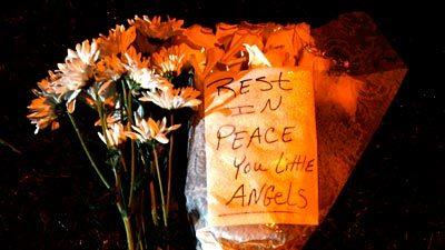 A note and flowers are left at a makeshift memorial to victims of the Sandy Hook Elementary School massacre in Newtown, Conn.
