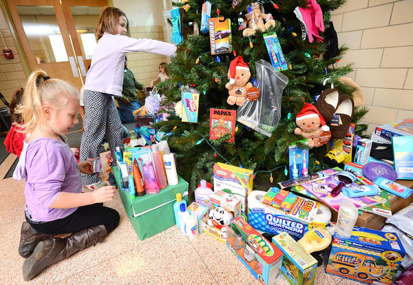 Fountaindale Elementary School second-graders Morgan Witmer, left, and Rachel Boschen, standing at center, organize more than 600 gifts around the school's giving tree Monday afternoon. The gifts will be given to Citizens Assisting and Sheltering the Abused, or CASA.