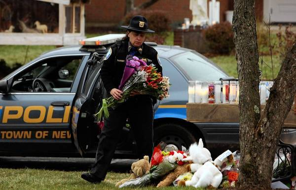 A Newtown police officer prepares to leave flowers at a memorial for victims of the Sandy Hook Elementary School shooting.