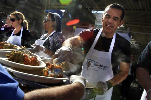 Mayor Antonio Villaraigosa serves food at the Thanksgiving dinner at the Midnight Mission. On hand was a staggering amount of food, including 4,000 pounds of turkey, 3,000 rolls, 700 pounds of candied yams, 400 pies and 15 gallons of gravy. But what was most impressive to some diners was the festive environment and the chance to experience holiday cheer with others.