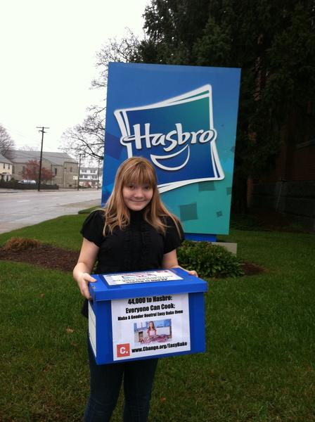 McKenna Pope in front of Hasbro headquarters in Pawtucket, R.I., with a box of some of the 44,000 signatures on her Change.org petition.