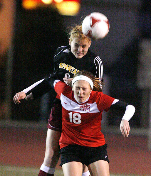 La Canada's Kara Lankey jumps over Glendale's Meghan Spencer to head the ball in the first half of a non league girls soccer match at Glendale High School on Monday, December 17, 2012.