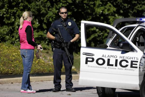 An armed police officer talks to a woman outside Cambridge Elementary School in San Antonio. The campus and others in the district were locked down after a caller threatened to shoot students.