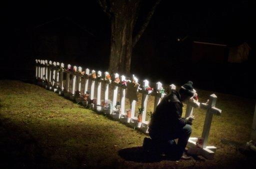 Frank Kulick tends a Sandy Hook memorial on his front lawn in Newtown, Conn.