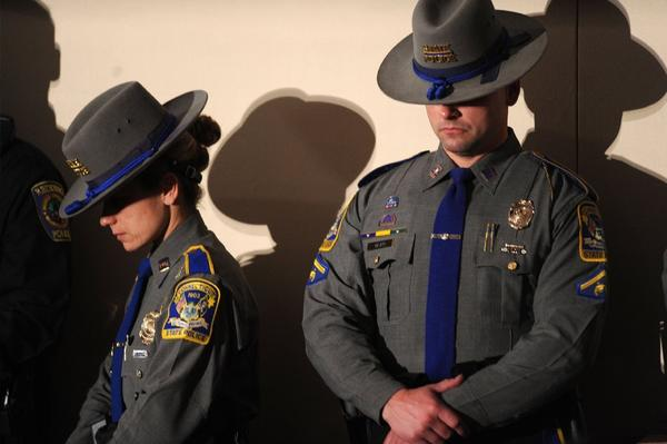 Connecticut State Troopers bow their heads during an interfaith vigil for the shooting victims from Sandy Hook Elementary School.