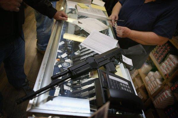 A customer purchases an AK-47 style rifle in Tinley Park, Ill. Gun sales have surged recently following the mass shooting in Connecticut.