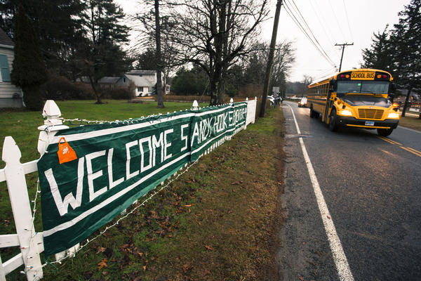 A school bus drives past a welcome sign outside of the entrance for Chalk Hill Middle School where students displaced from Sandy Hook Elementary School will begin their classes on Tuesday.
