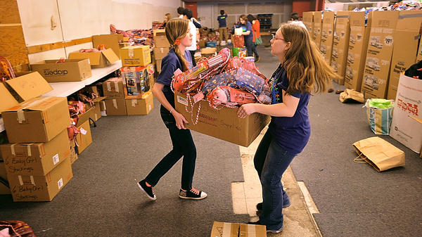 Volunteers Meghan Leatherman, left, and Haley Kaiser hoist a box full of Christmas stockings Friday. They were preparing for the Salvation Army Toys for Tots give-away at Long Meadow Shopping Center. They are students at Grace Academy.