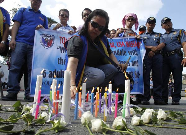 A Filipino human rights activist lights candles and offers prayers for victims, who were killed in a shooting at Sandy Hook Elementary School in Newtown, Connecticut in the U.S., during a prayer vigil in front of the U.S. embassy in Manila December 18, 2012.