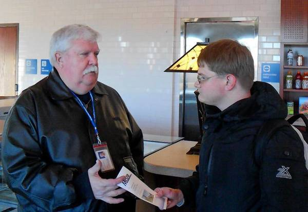 Tom Donegan, who manages emergency preparedness training at Metra, recently passed a safety brochure to Tinley Park resident Steven Brinkley at the 80th Avenue Metra station.