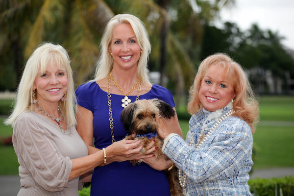 "June Miller, left, Christy Gumberg and Jonelle Milton cuddle a pup while promoting the seventh annual ""Angel PAWS Luncheon and Fashion Show,"" which will take place Jan. 23 at the Coral Ridge Country Club. PAWS is an auxiliary of the Humane Society of Broward County."