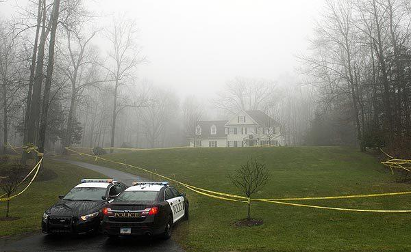Police cruisers are stationed Tuesday outside the home of Nancy Lanza, where she lived with her son, Adam Lanza, in Sandy Hook, Conn. Nancy Lanza was her son's first victim Friday before he went on a shooting rampage at Sandy Hook Elementary School.
