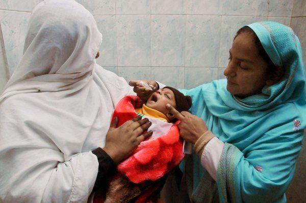 Health workers in Peshawar, Pakistan, give a polio vaccine to a child during a three-day nationwide vaccination campaign.