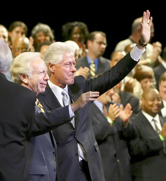 Former US president Bill Clinton (R) waves with Senator Joseph I. Lieberman (L), D-CT, during a Lieberman campaign rally at the Palace Theater in Waterbury, Connecticut. Lieberman was in a highly contested fight for the Democratic nomination against Greenwich businessman Ned Lamont.