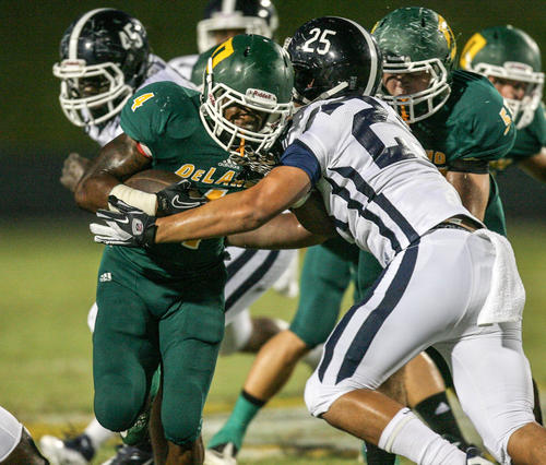 Deland's JoJo Kemp (4) slips past Dr Phillips' August Amone (25) as he runs for yardage during second quarter action of a high school football game against Dr. Phillips at the Spec Martin Stadium in Deland, Fla. on Friday, September 28, 2012.