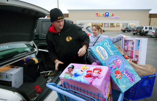 Tim Lazzara, left, and his fiance Natalie Bronge pack their car after buying toys for children in their families, at a Toys R Us in Downers Grove.