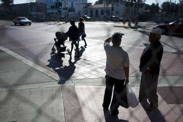 Pedestrians wait before crossing the street at Compton Boulevard and Willowbrook Avenue across from City Hall in Compton.