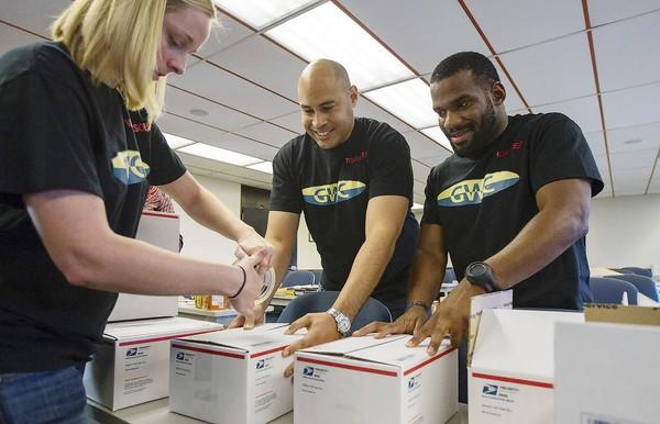 Veterans Tabatha Maddox, left, Jeffrey Saunders, center, and Joshua Ellis with the Goldenwest College Student Veteran Organization put together gift packages to send to troops overseas at the school last Thursday.