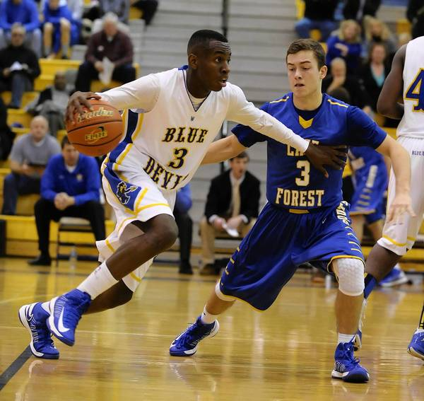 Warren's Aarias Austin drives against George Quall. Lake Forest defeated Warren 36-28 on Dec. 14 at Warren High School in Gurnee.