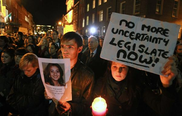 Protesters in Dublin hold pictures of Savita Halappanavar as they gather outside the Irish Parliament building during a demonstration in favor of abortion legislation.