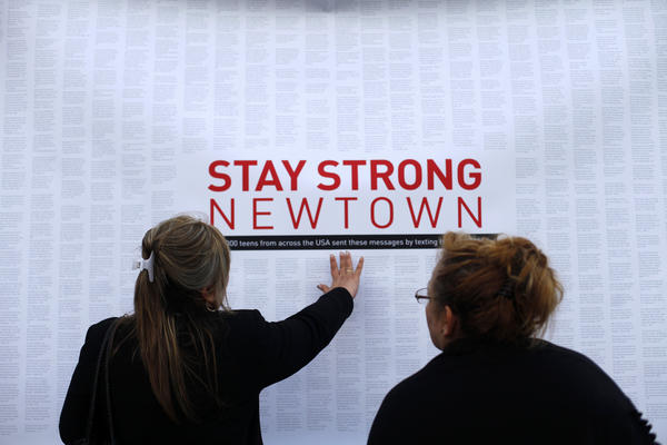 A woman touches a printout of messages from teenagers around the United States at a memorial for the victims of the Sandy Hook Elementary School shooting in Newtown.