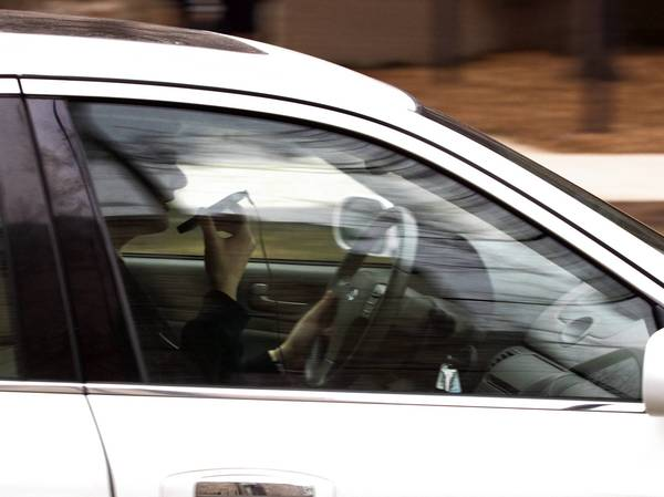 A driver uses a cell phone while behind the wheel in Evanston, Thursday, March 1, 2012.