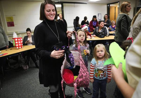 Jackie Tausend, left, drops off a donation of winter wear with daughters Madyson, 6, center, and Abygail, 3, during a holiday clothing drive at Madyson's Girl Scout meeting this month. Tausend's grandmother gives her grandchilden and great-grandchildren $50 apiece every year to do something for charity during the holidays.