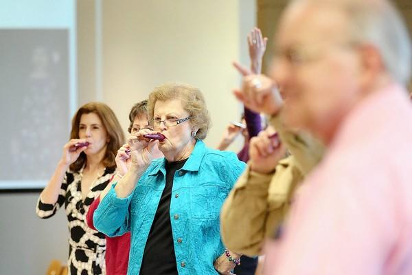 Retired information specialist Jean Soto, center, of Columbia, plays the kazoo while Vladimir Marinich, one of the original professors at Howard Community College, walks into his surprise retirement party at Howard Community College.