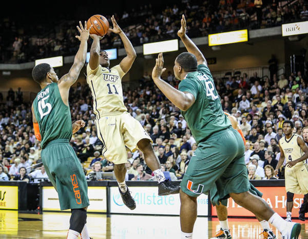 UCF's Calvin Newell (11) shoots over Miami's Reggie Johnson (42) during first half action of a NCAA basketball game against the University of Miami at the UCF Arena in Orlando, Fla. on Tuesday, December 18, 2012.