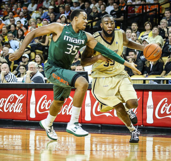 UCF's Keith Clanton (33) drives past Miami's Kenny Kadji (35) during second half action of a NCAA basketball game against the University of Miami at the UCF Arena in Orlando, Fla. on Tuesday, December 18, 2012.