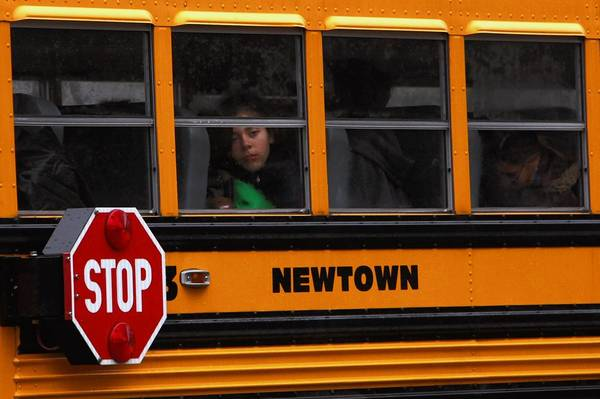 A girl peers from a school bus as classes resumed for most students Tuesday and funerals for victims of the school shooting continued in Newtown, Conn.