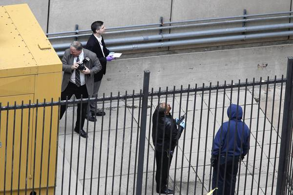 Investigators view the outside of the Metropolitan Correctional Center in downtown Chicago after two prisoners escaped from the building. Authorities discovered them missing from their cell at about 8:45 a.m.