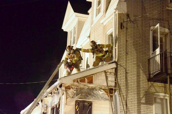Firefighters look for hot spots above the porch roof at 1702 Seidersville Road, Salisbury Township, after a fire gutted the porch and forced a family of six to evacuate Tuesday night. No one was injured in the blaze.