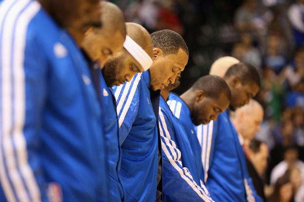Shawn Marion, center, and the rest of the Dallas Mavericks take a moment of silence for the victims of the shooting that took place at Sandy Hook elementary school in Newtown, Connecticut prior to the game against the Philadelphia 76ers at American Airlines Center on December 18, 2012 in Dallas, Texas.